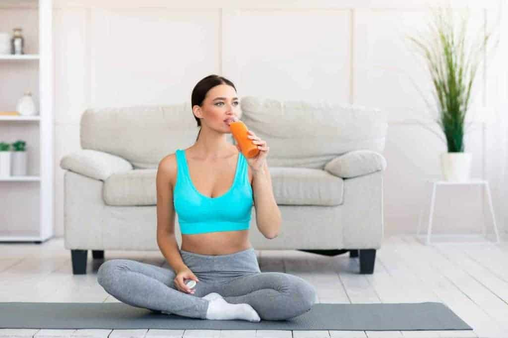 Fit Woman Enjoying Fruit Juice Exercising At Home, Empty Space