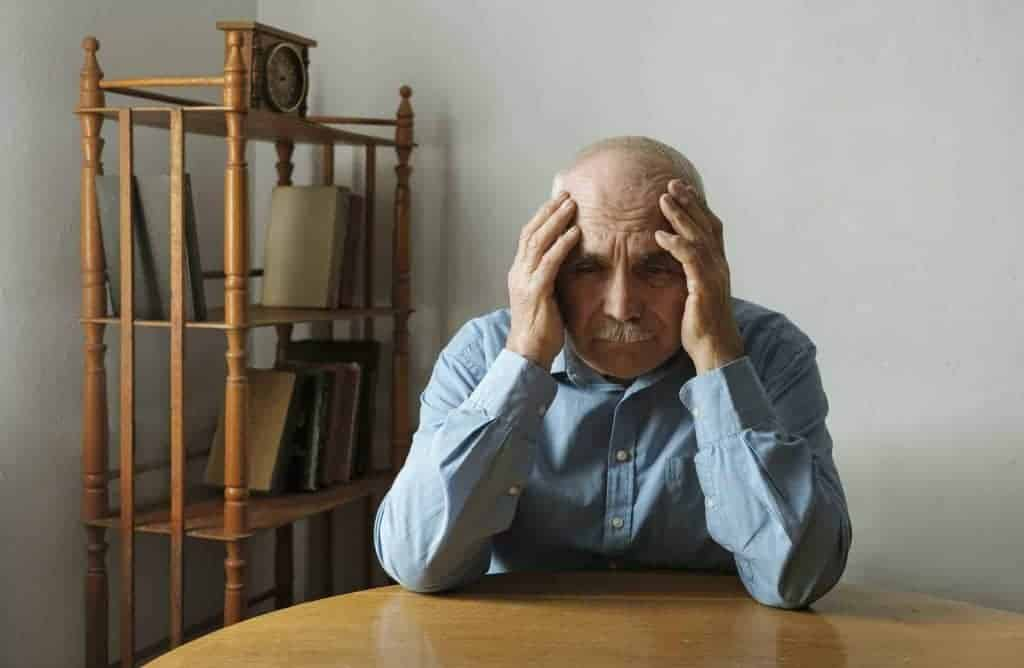 Worried elderly man with his head in his hands